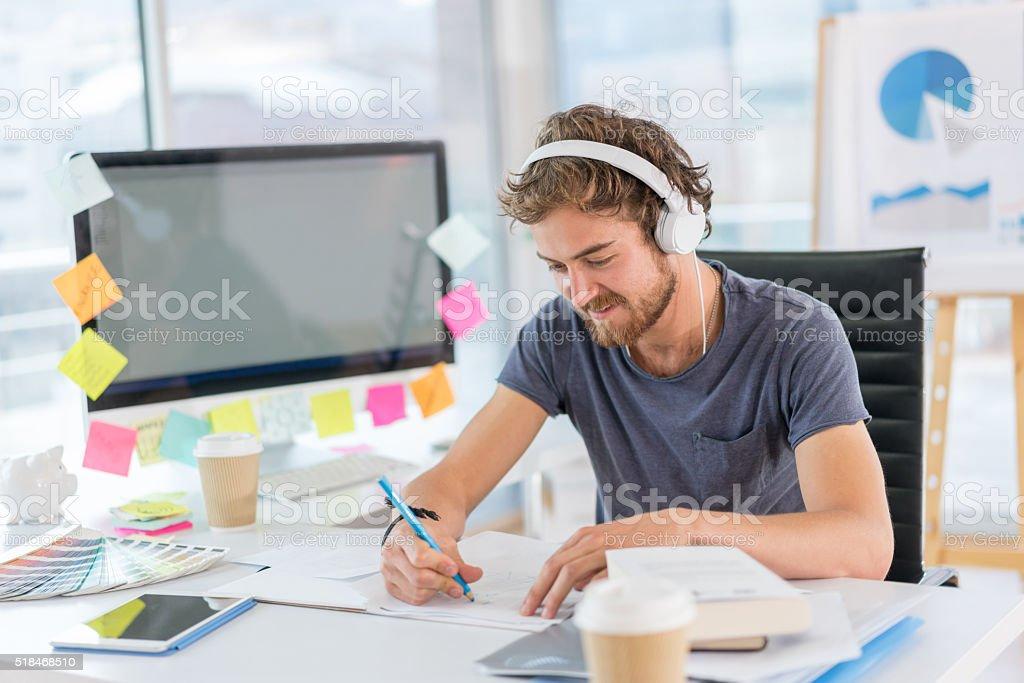 Graphic designer working and listening to music stock photo
