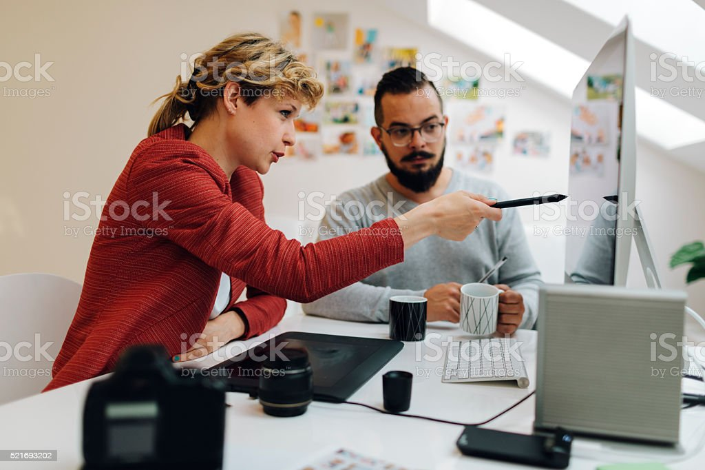 Graphic Designers Cooperating At Work. stock photo
