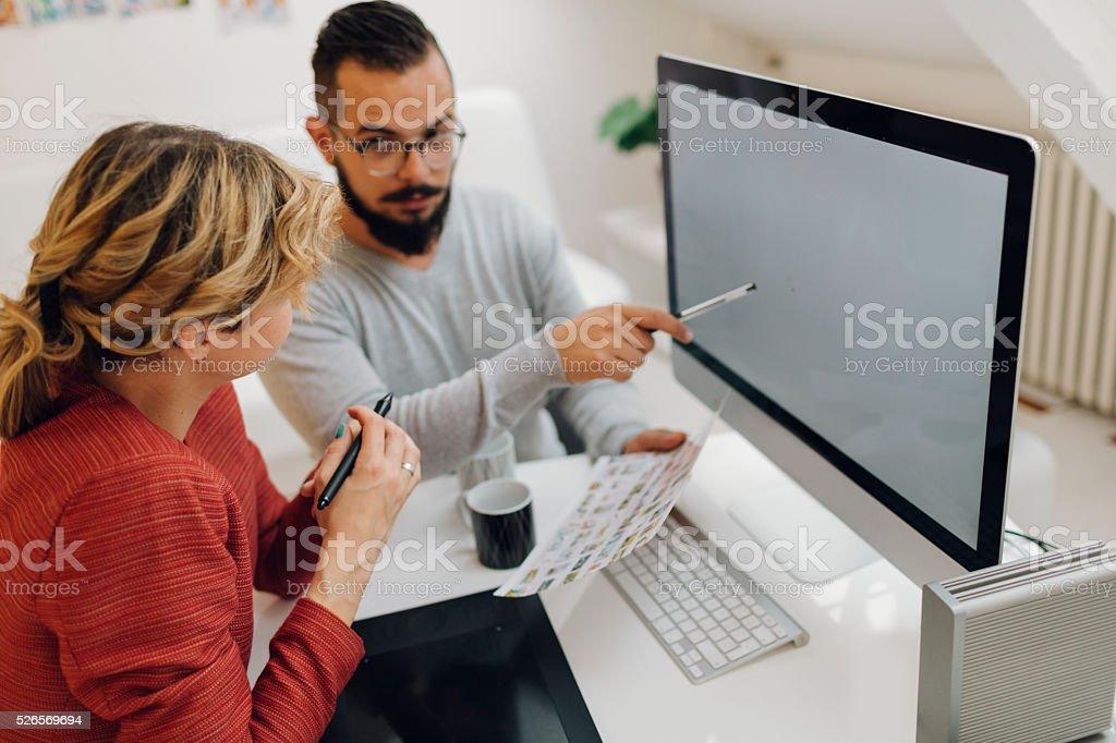 Graphic Designers Cooperating At Work. stock photo