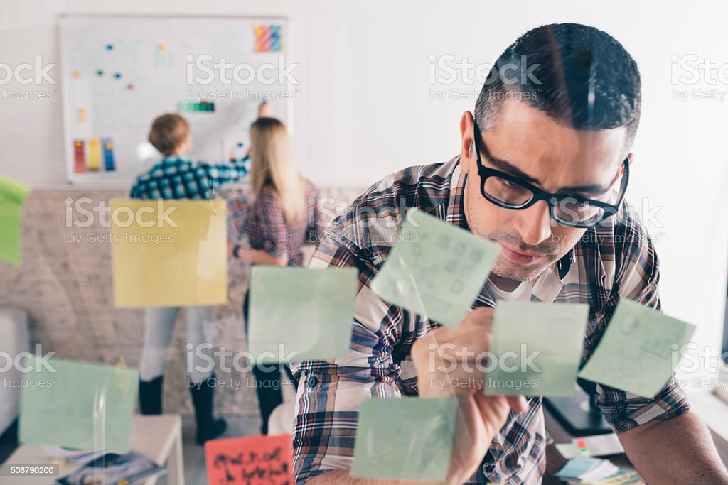 Graphic designers putting ideas on sticky notes on glass stock photo