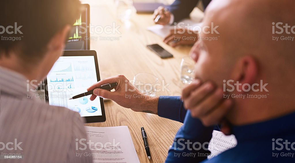 Graphic information being displayed on a tablet during business meeting stock photo