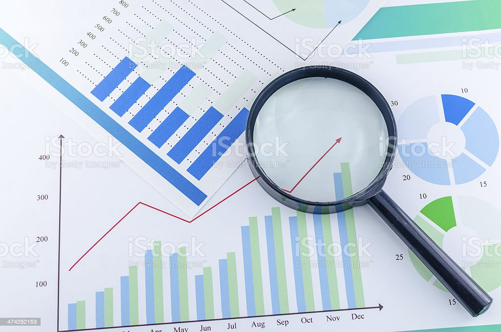 Graphs and Magnifying glass stock photo