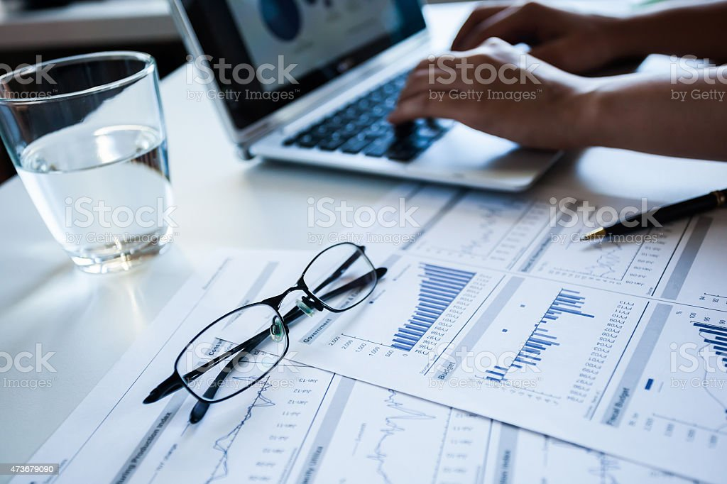 Graphs beside a laptop with spectacles and a glass of water stock photo