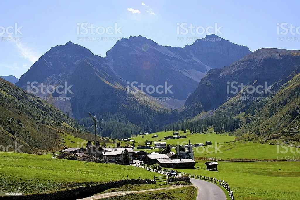 Grass alpine meadow and village in Swiss Alps, Switzerland. stock photo