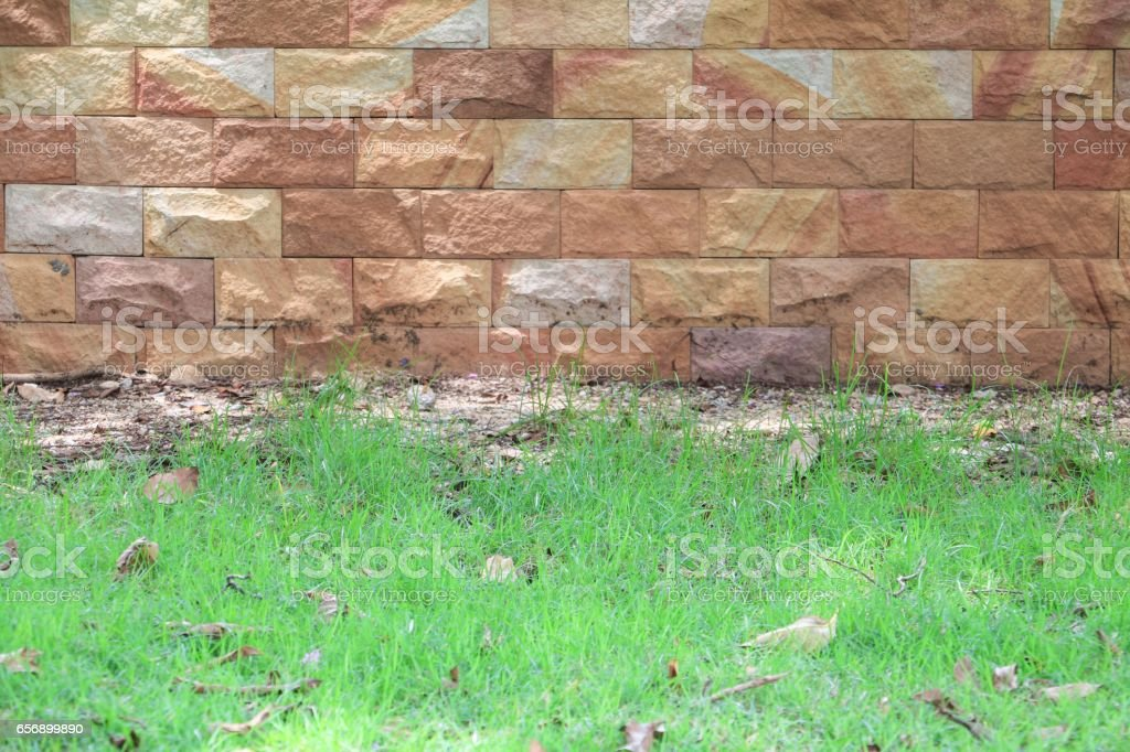 grass and sandstone brick wall texture background stock photo