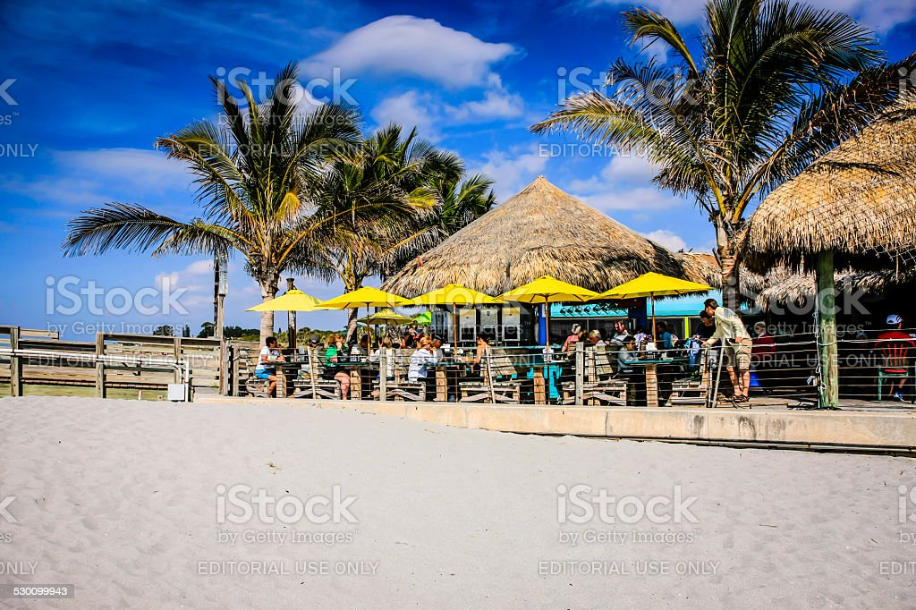 Grass roofed tiki bar on Venice beach FL stock photo