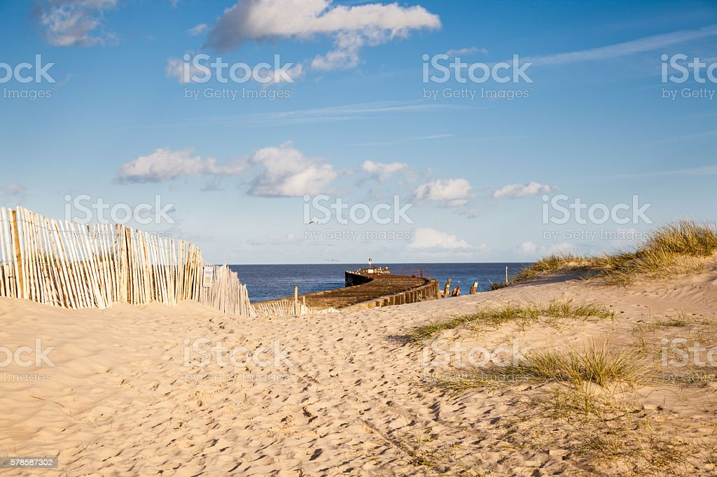 grass sand dunes and pier with footprints Walberswick Suffolk England stock photo