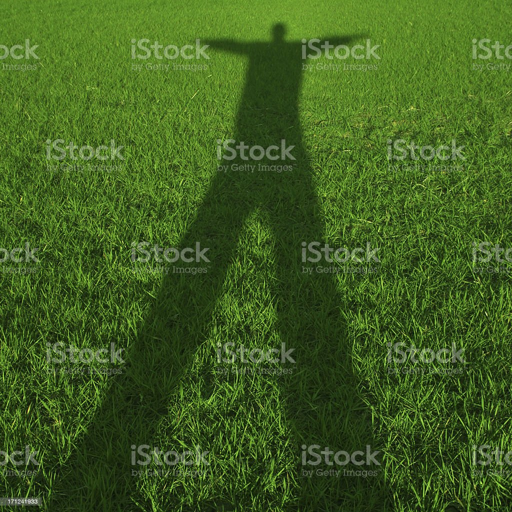 Grass shadow - arms out stock photo