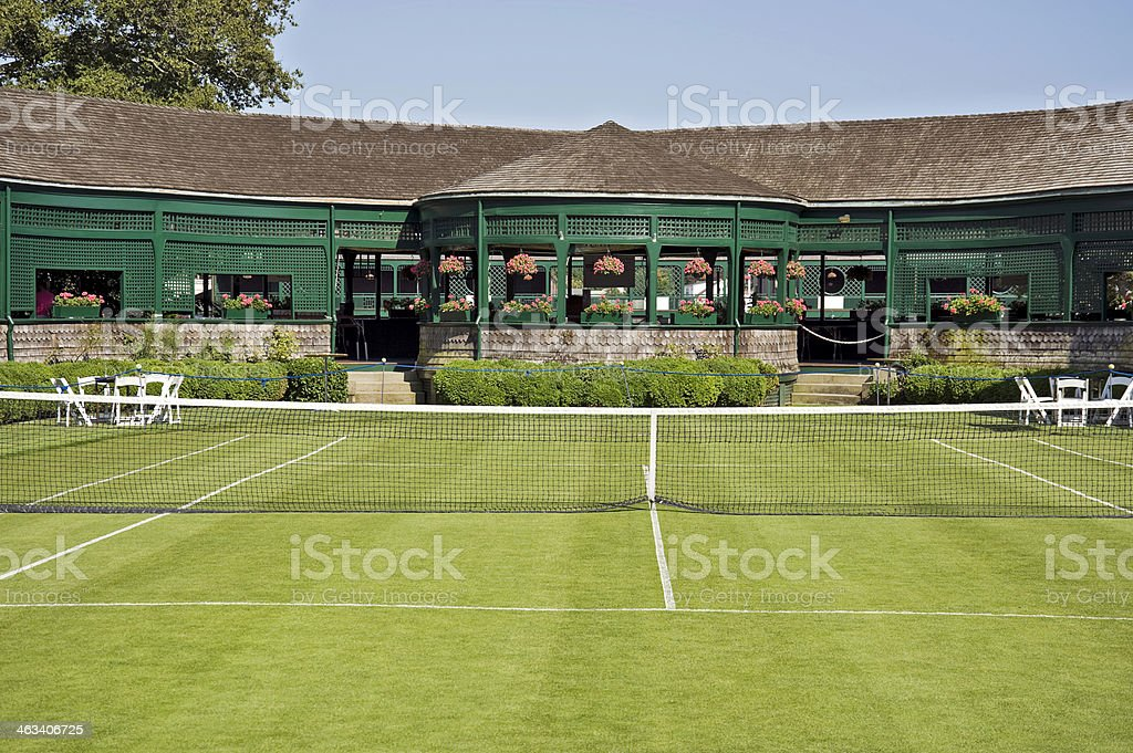 A grass tennis court with pavilion in the background stock photo