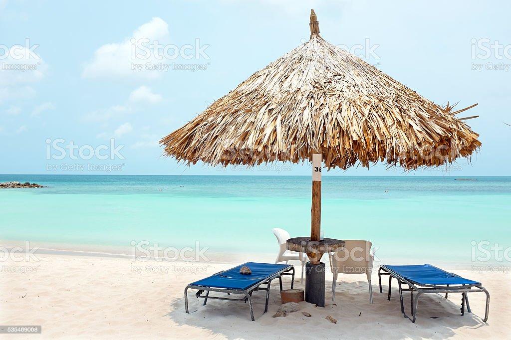 Grass umbrella at the beach on Aruba island stock photo