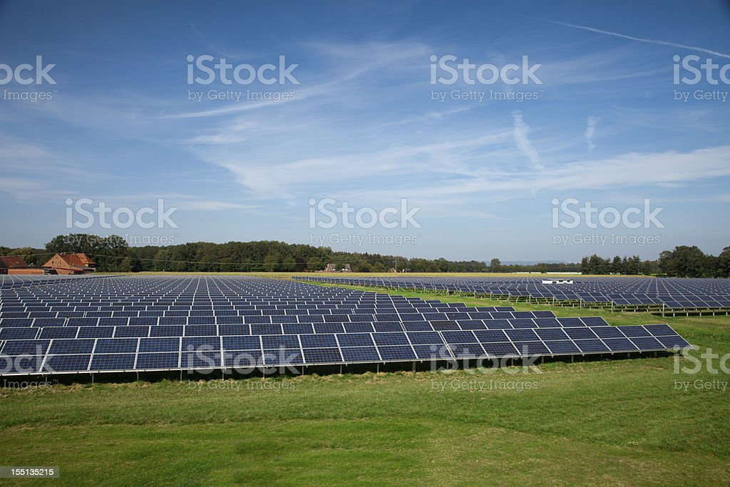 A grassy field filled with solar panels royalty-free stock photo