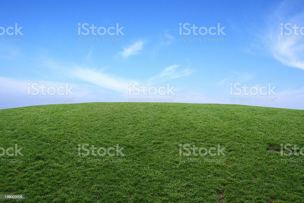 Grassy hill and skies royalty-free stock photo
