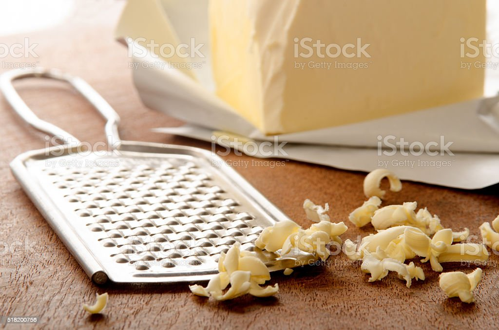 grated butter on wooden board stock photo