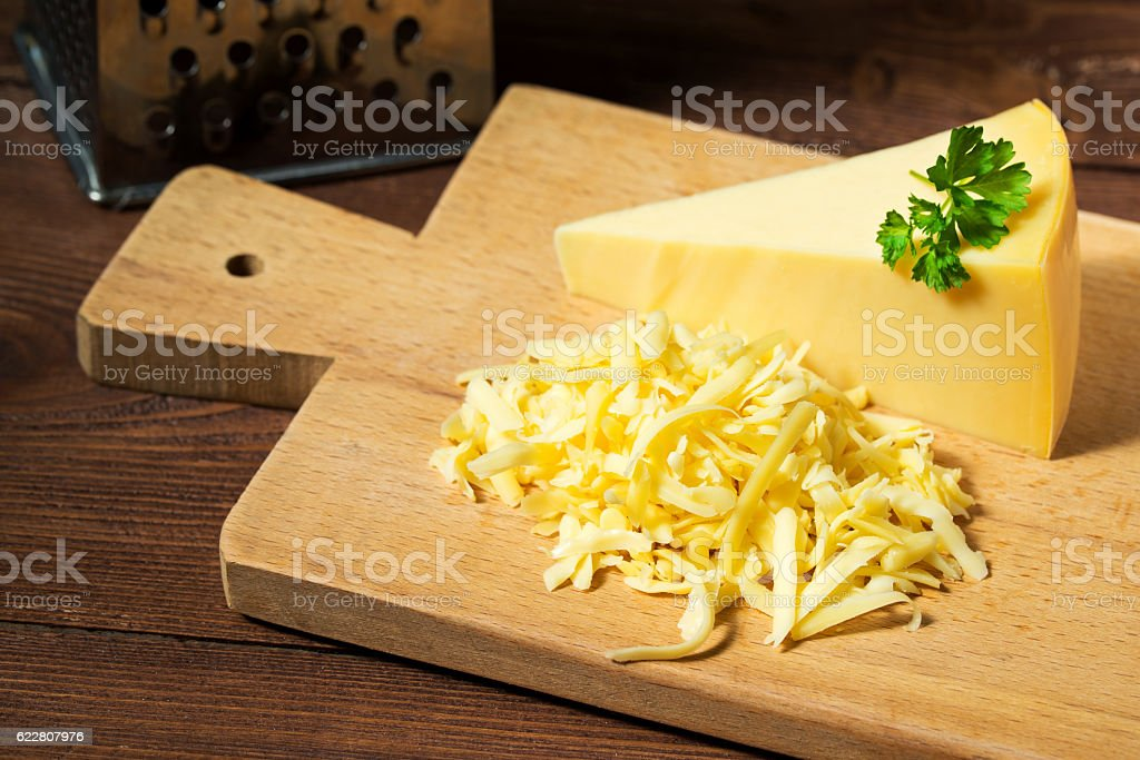 Grated cheese and cheese triangle, wooden cutting board stock photo