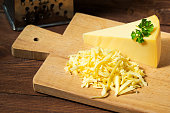 Grated cheese and cheese triangle, wooden cutting board