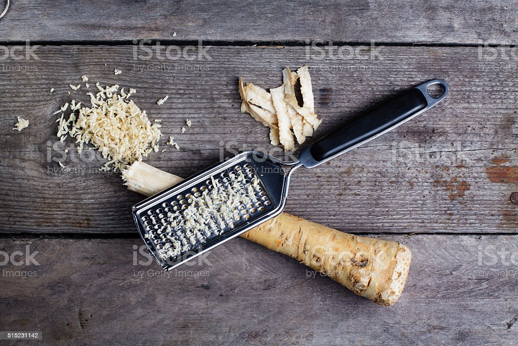 Grated horseradish root with grater on wooden gray table. stock photo
