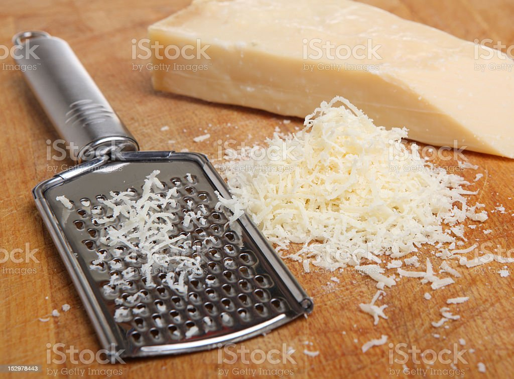 Grated Parmesan cheese in a pile next to a block of cheese stock photo