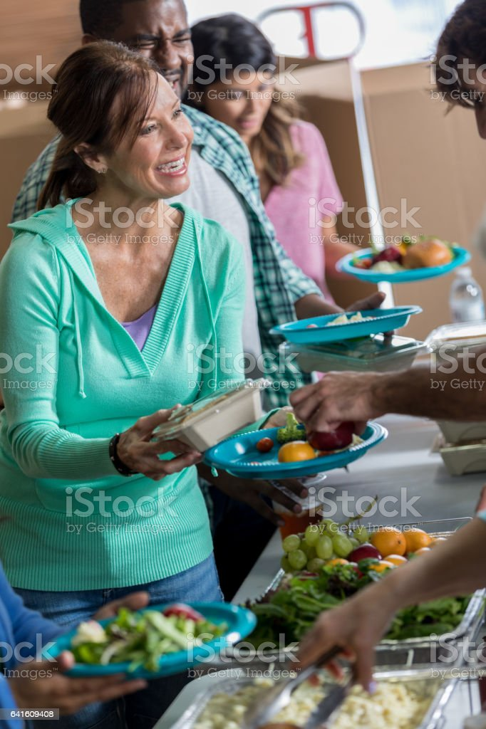 Grateful woman receives meal in soup kitchen stock photo