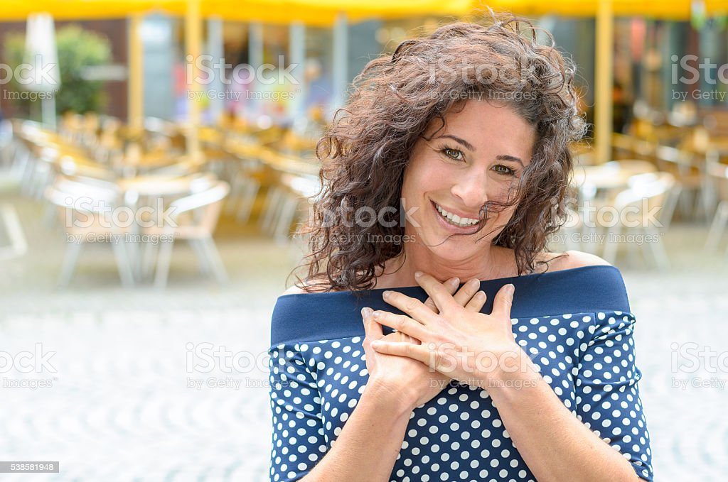 Grateful young woman with her hands to her heart stock photo