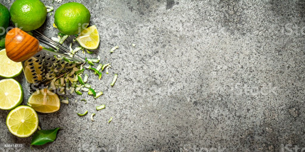 Grater with fresh limes . stock photo