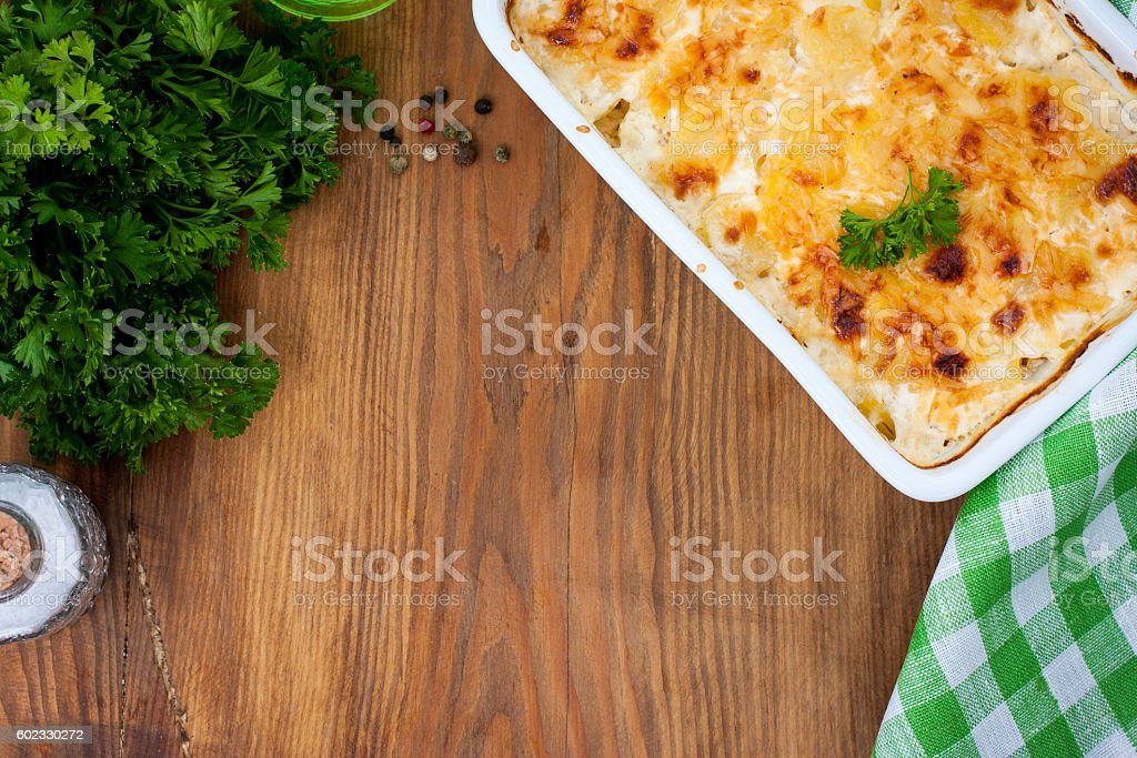 Gratin potatoes on a wooden table, top view stock photo