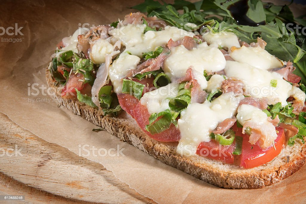 gratinated bread on a rustic wooden board stock photo