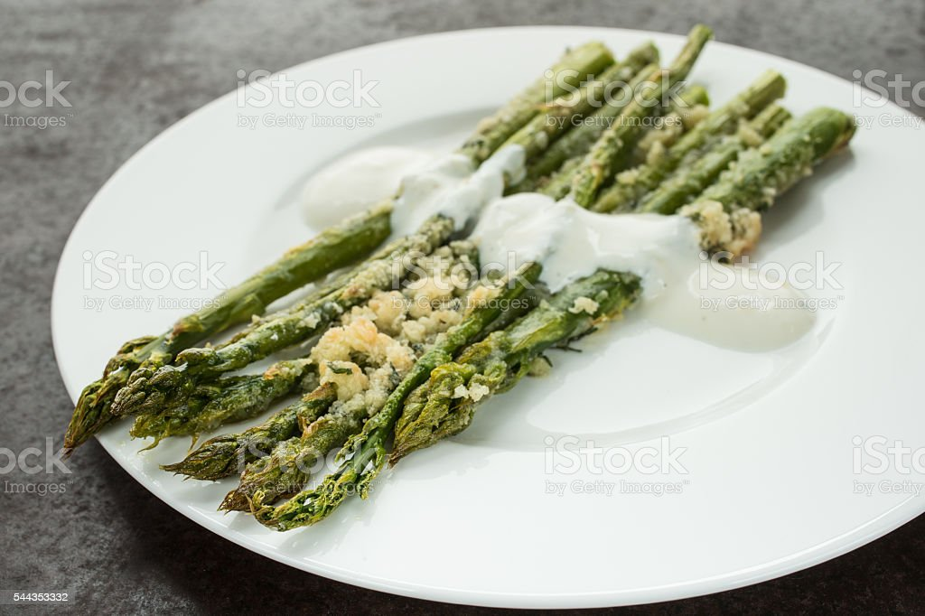 Gratinated green asparagus with white sauce and parmesan cheese stock photo