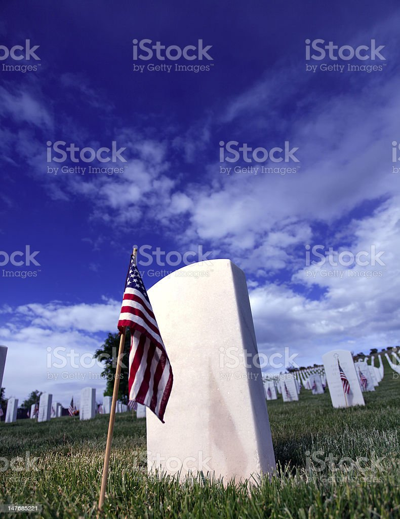 Grave Marker of Soldier with Flag in a National Cemetery. stock photo