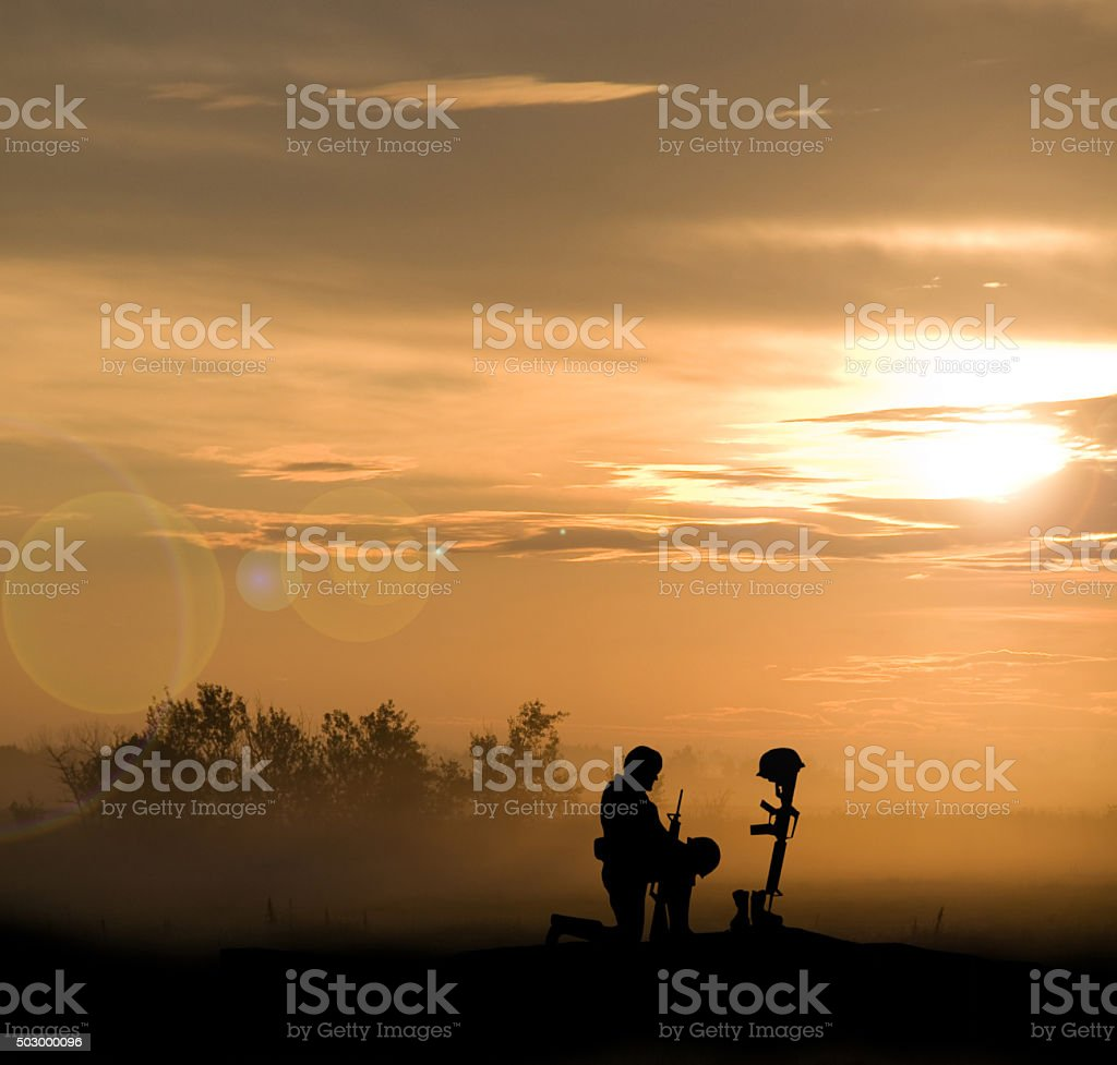Grave of Fallen Soldier and Kneeling Comrade stock photo
