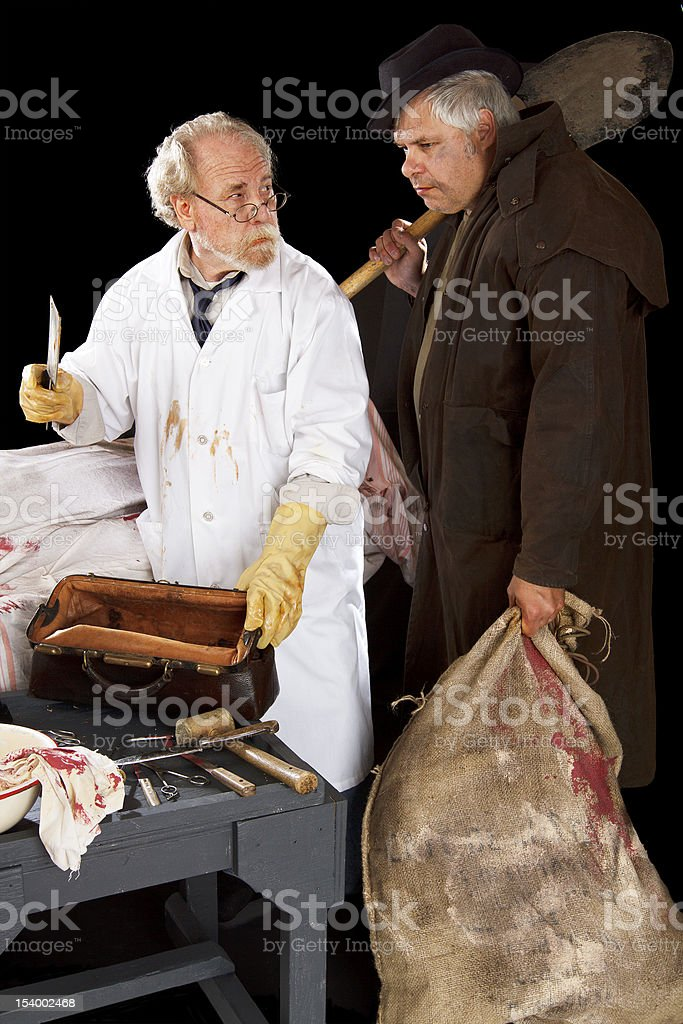 Grave robber and evil doctor with bloody cleaver exchange glance stock photo