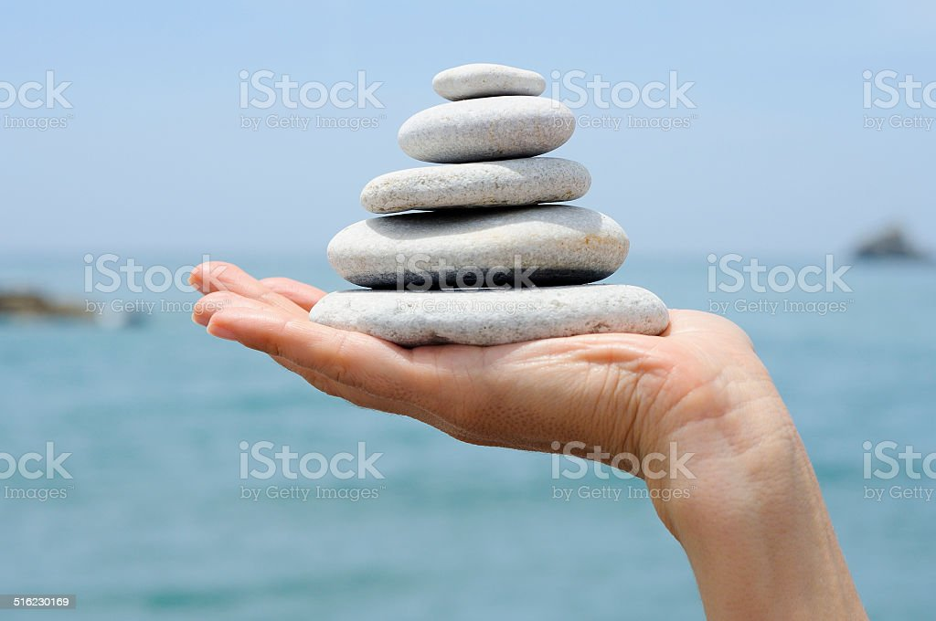 Gravel pile in woman's hands with sea background stock photo