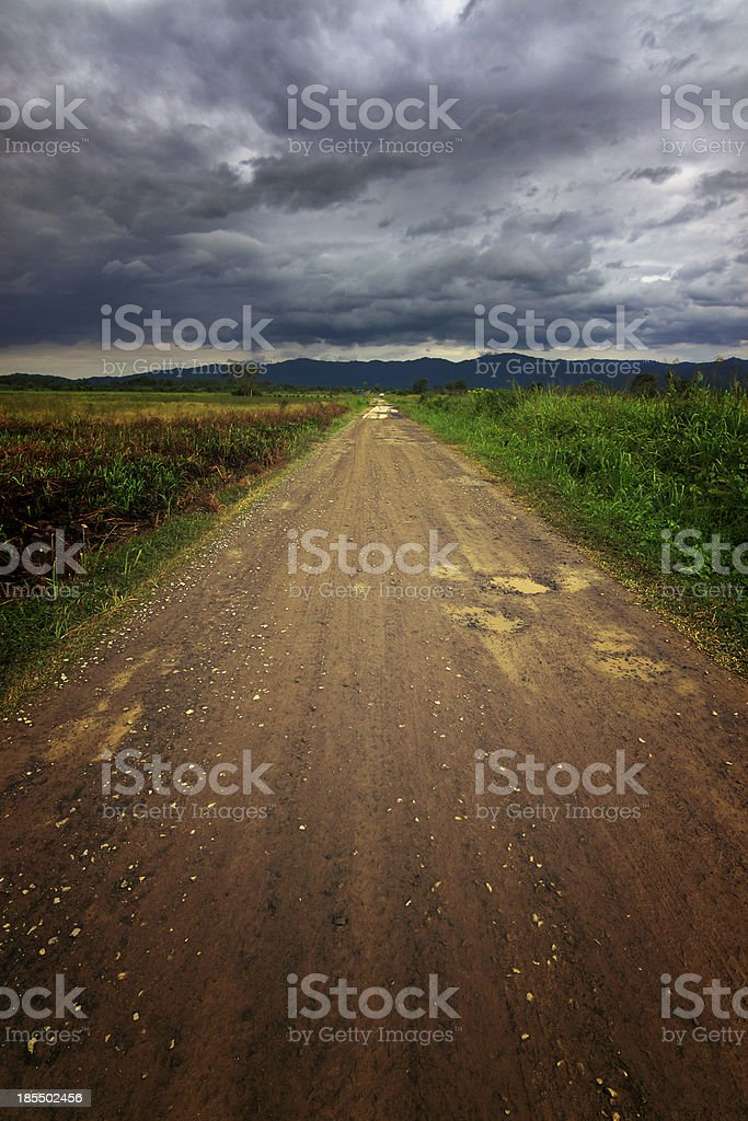 Gravel road leading to stormy skies royalty-free stock photo