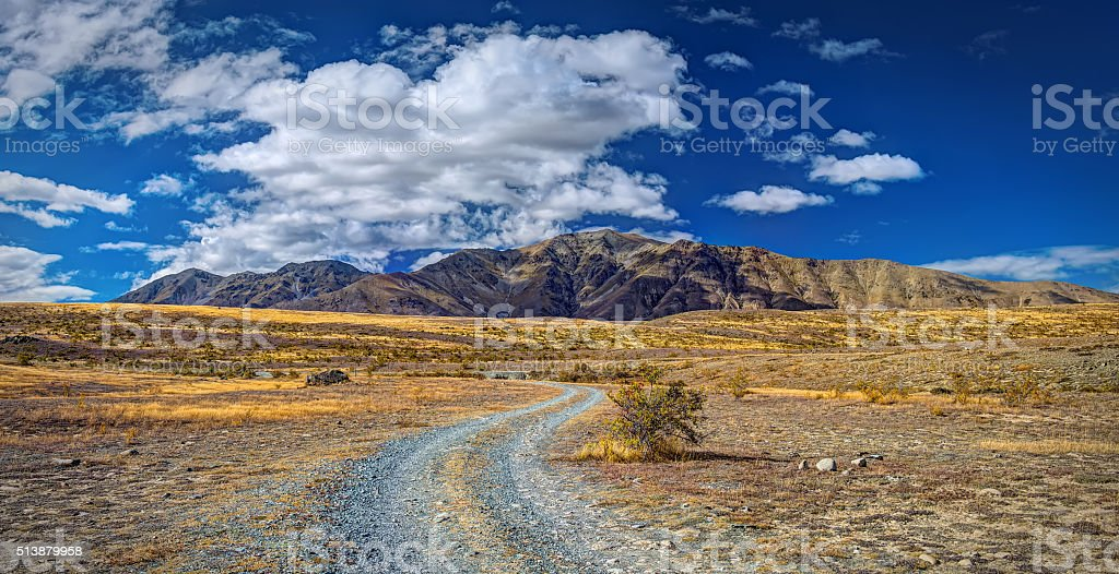 Gravel Road Towards Mount Dobson With Cloudy Sky stock photo