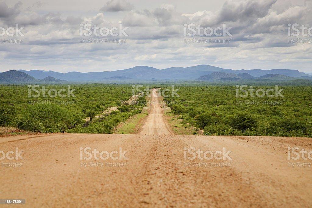 Gravel road with Zebra Mountains in Namibia stock photo