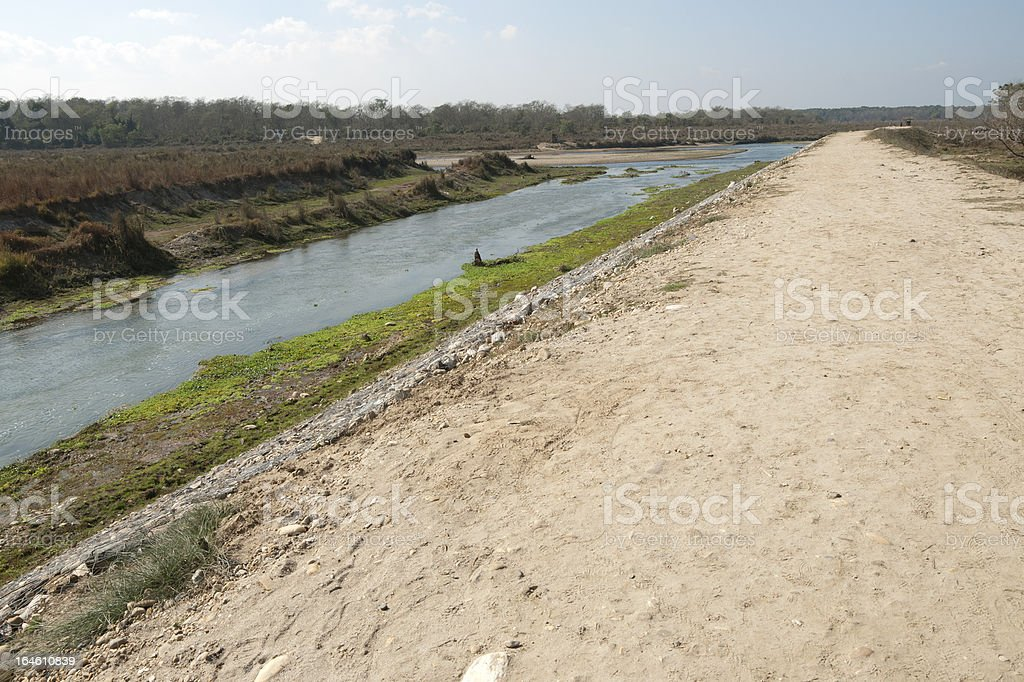 Graveled road alongside the river stock photo