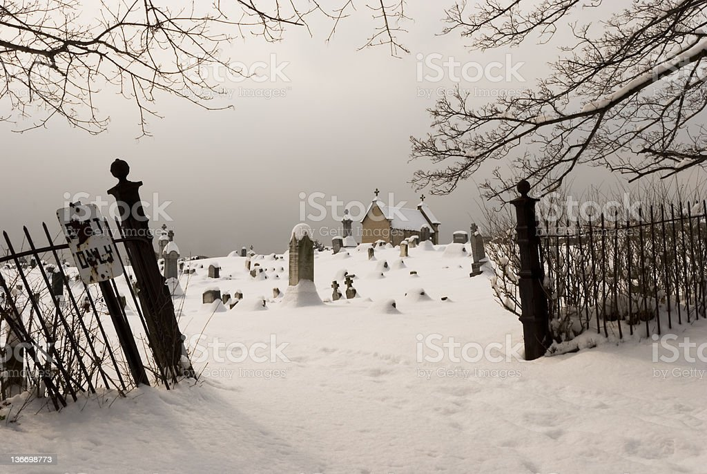 Graveyard Entrance in Snowy Overcast Winter Day, Cemetery View royalty-free stock photo