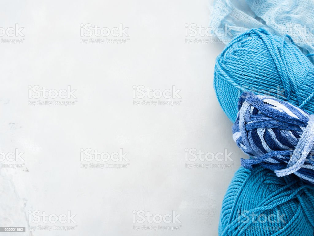 Gray background with colorful yarn clews. Copy space stock photo