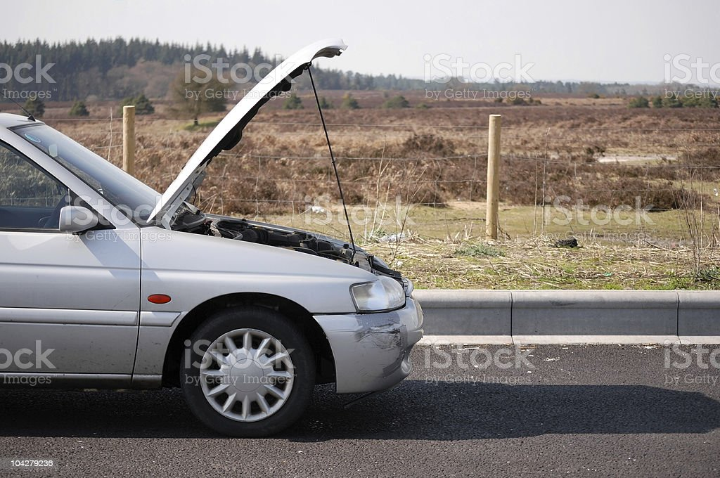 A gray car with its hood open parked by the side of the road stock photo