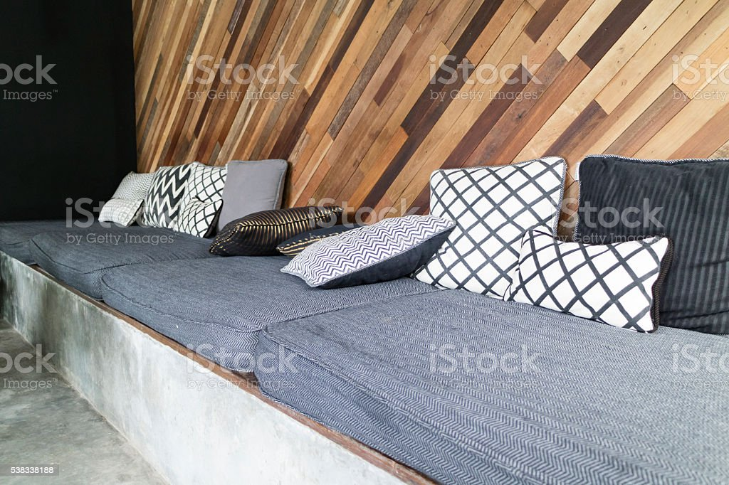 gray cushion and pillow with slant wooden wall stock photo