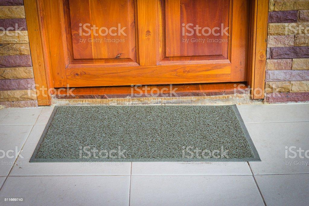 gray door mat  with close door stock photo