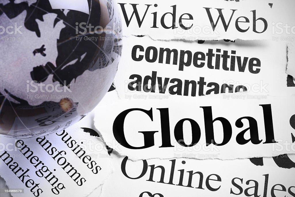 Gray glass globe paperweight on headlines about international Internet business stock photo