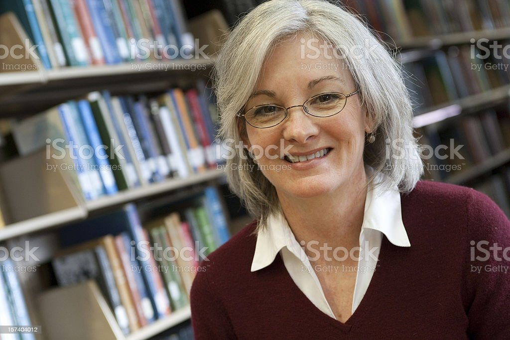 Gray haired woman smiling in front of shelves of books royalty-free stock photo