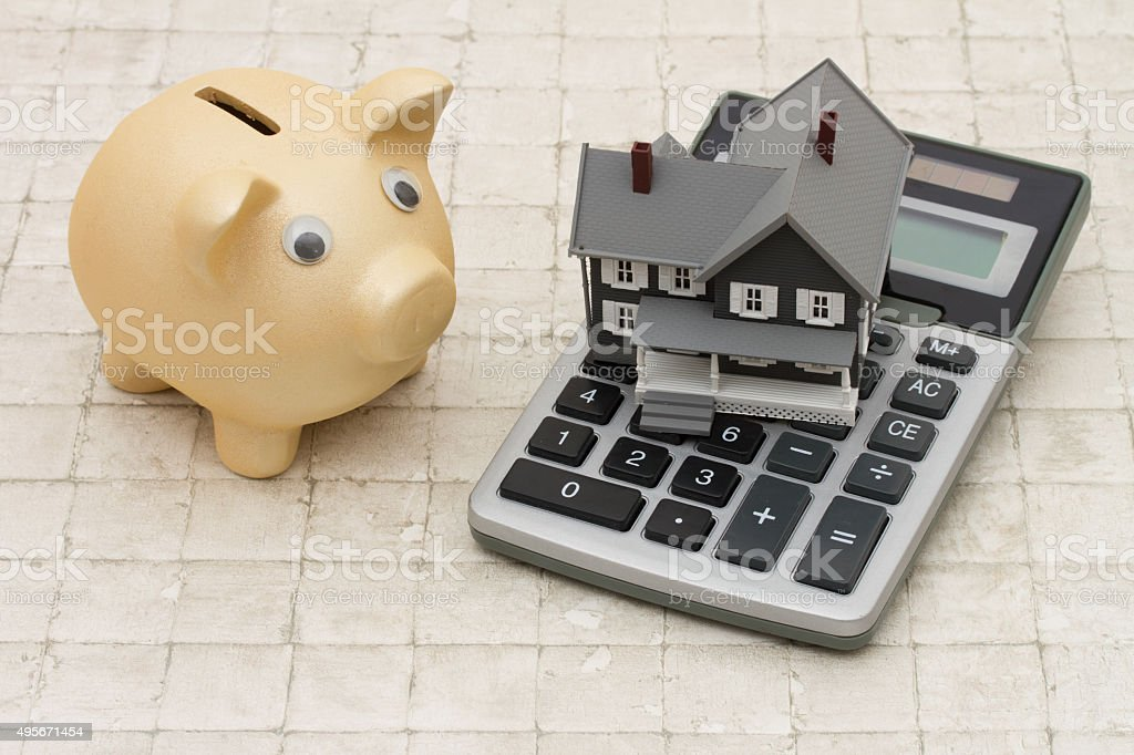 Gray house, piggy bank and calculator on stone background stock photo
