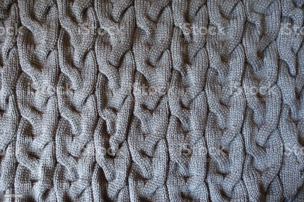 Gray knitted fabric with plait pattern from above stock photo