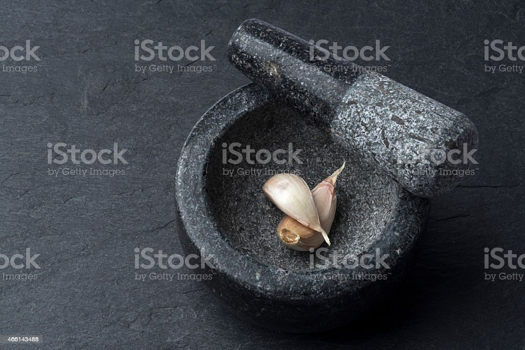 Gray mortar containing two cloves of garlic on a black table stock photo