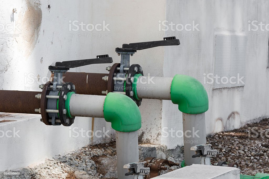 Gray old valve and old green water pipe. stock photo