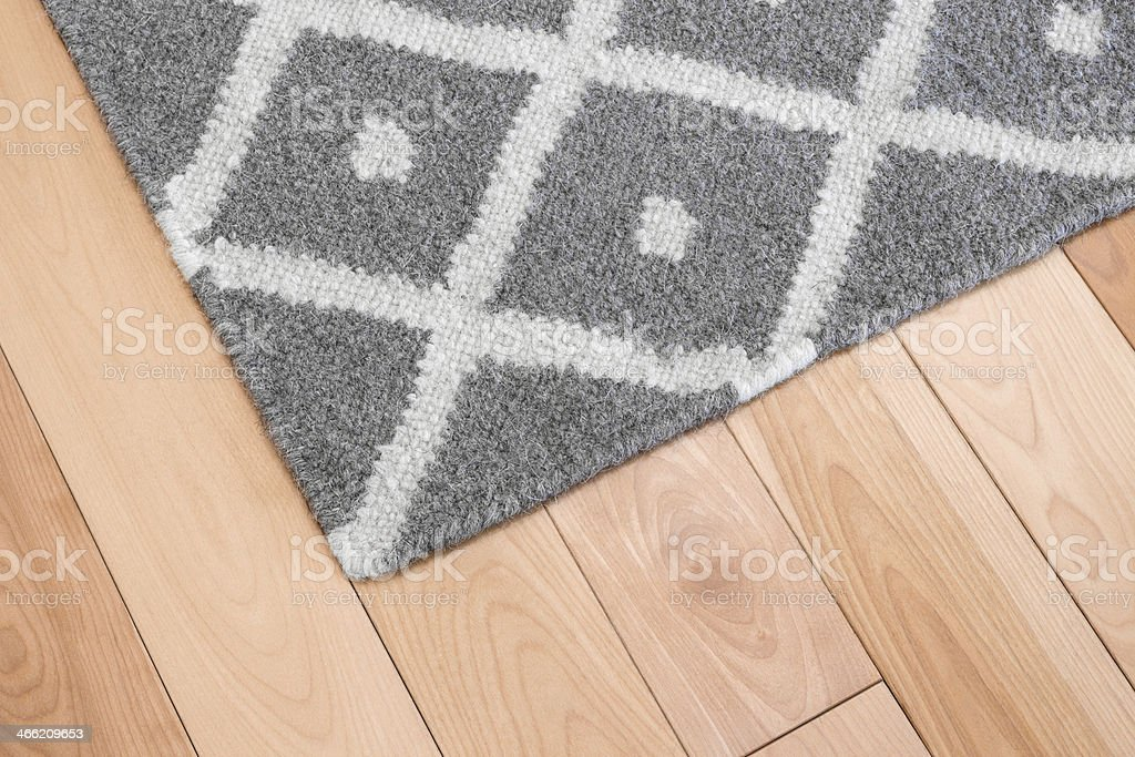 Gray rug on wooden floor stock photo
