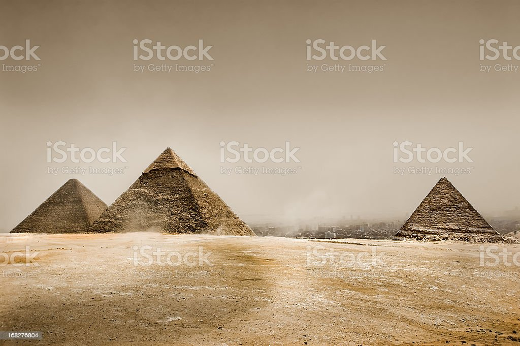 Gray sky in the desert with three pyramids stock photo