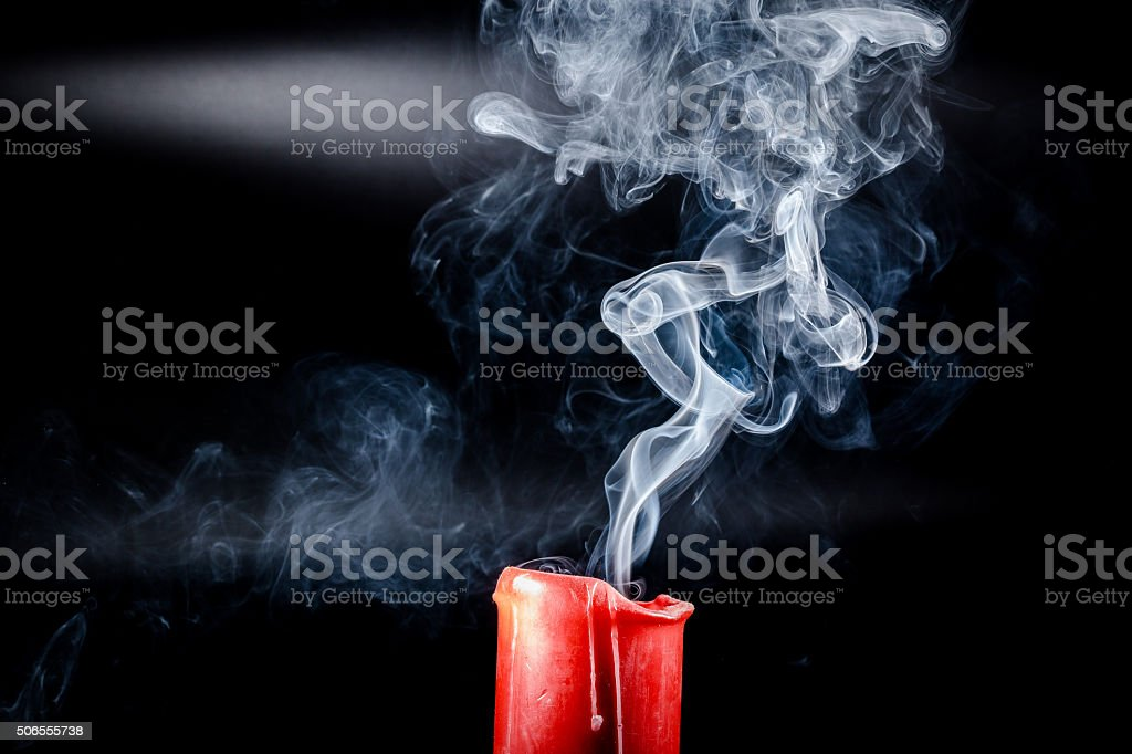 gray smoke flying upside from the extinct red candles stock photo