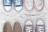 Gray sneakers and other shoes on white wooden floor background